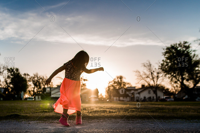 Girl dancing in field at sunset