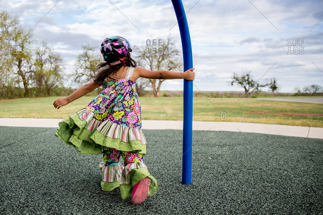 Girl in colorful dress swinging around pole at park