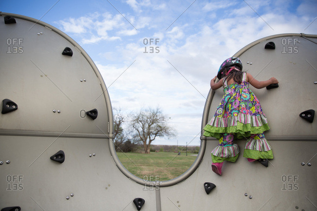 Girl in colorful outfit climbs on climbing wall