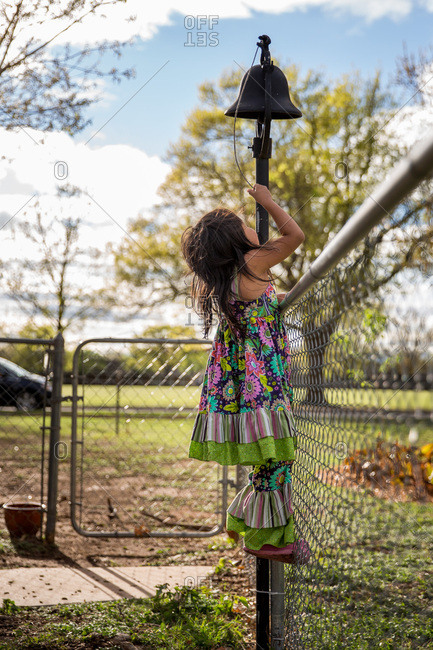 Girl climbing fence to ring bell