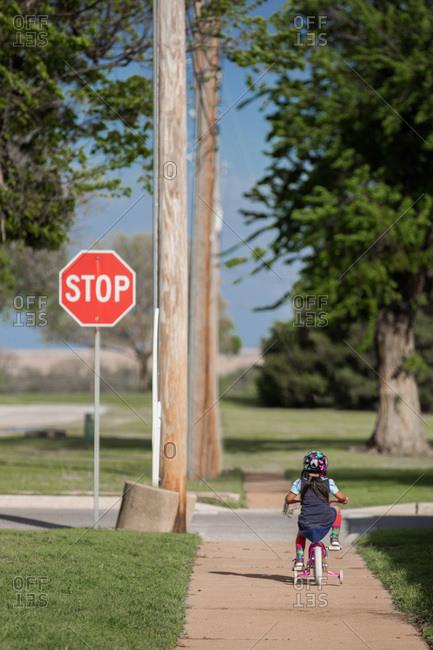 Young girl on bike with training wheels on sidewalk
