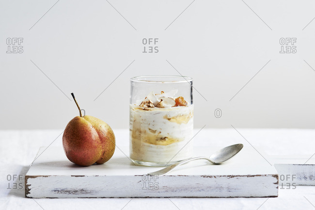 Glass of overnight oats, toppings and fresh pear on a table