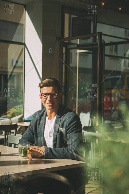 Smiling man sitting in a coffee shop with glass of tea