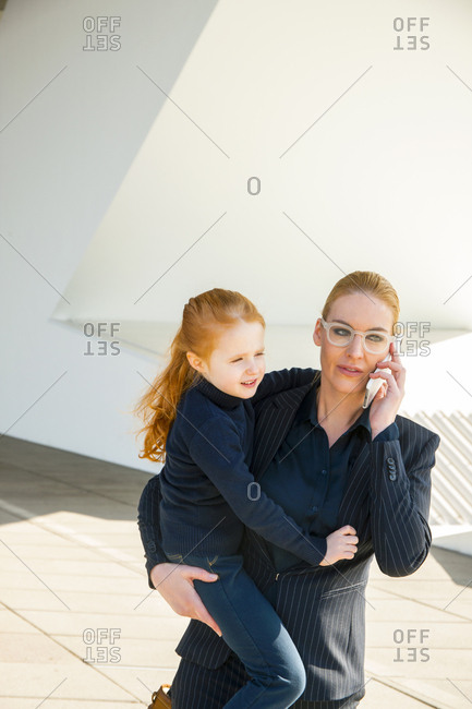 Businesswoman on the phone holding daughter