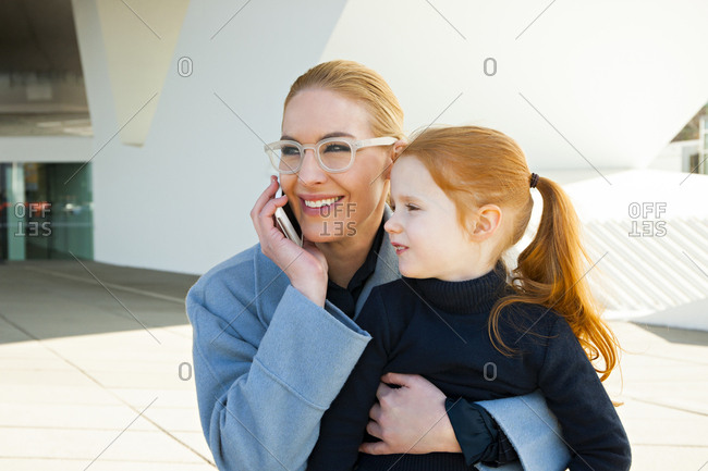 Smiling businesswoman on the phone hugging daughter