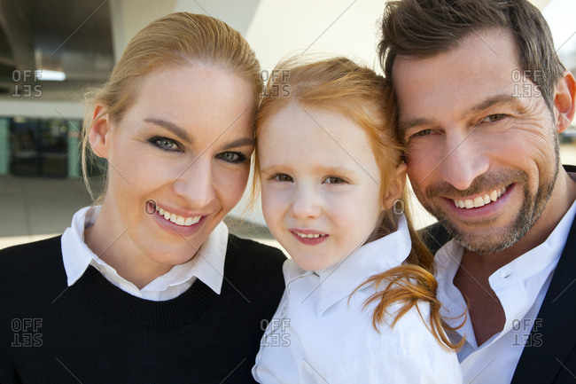 Portrait of smiling businessman and businesswoman with girl
