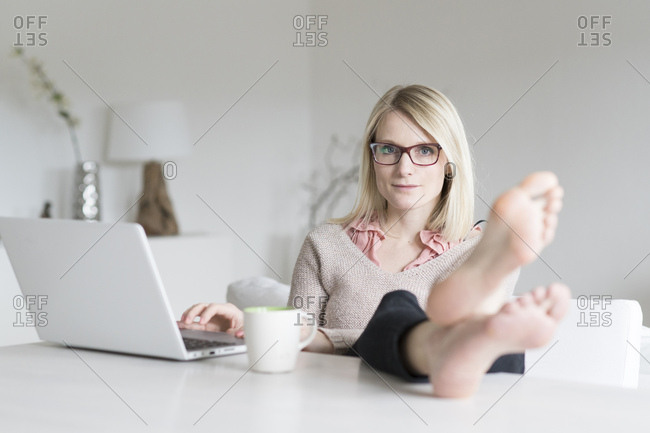 Portrait of blond woman at home sitting at table with feet up