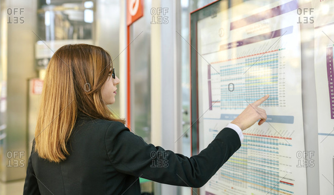 Businesswoman looking up timetable of public transport