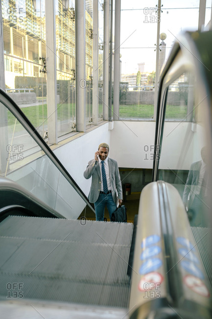 Businessman standing on escalator-  talking on his smart phone