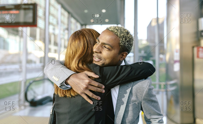 Young businessman and woman embracing at metro station
