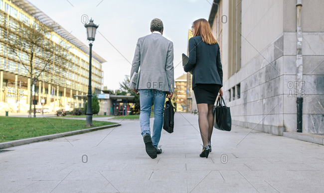 Young businessman and woman walking in the city
