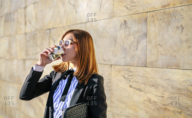 Businesswoman wearing sunglasses- having a coffee to go