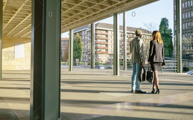 Young businessman and woman talking by office building