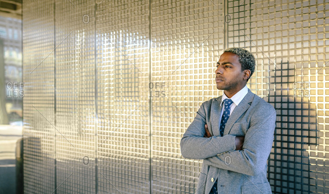 Businessman standing in front of golden wall with arms crossed