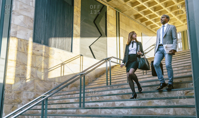Young businessman and woman climbing stairs