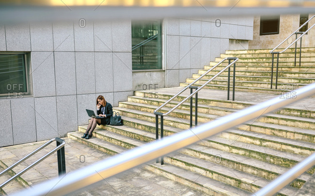 Businesswoman sitting on stairs- using laptop