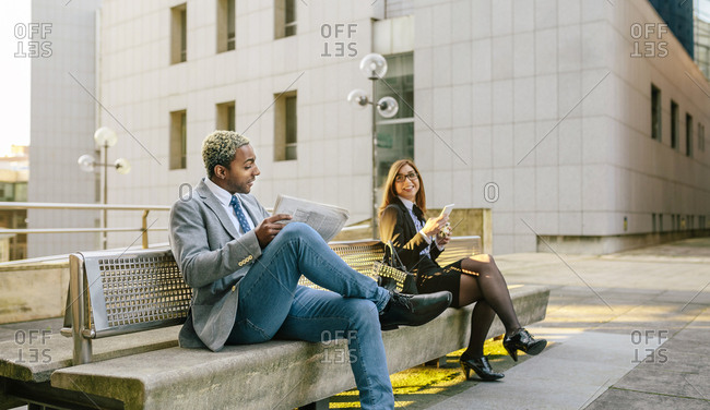 Young businessman and woman sitting on bench- talking