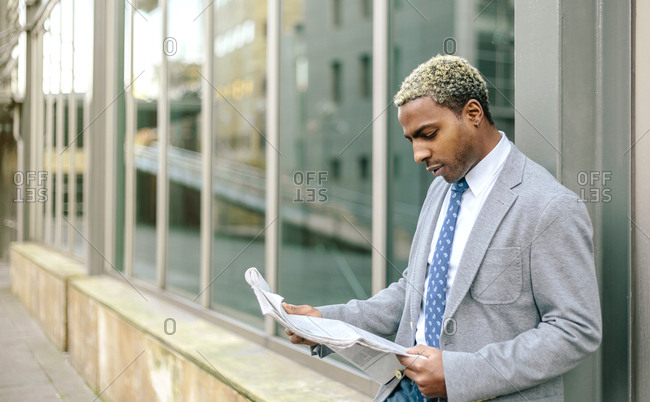 Businessman leaning against wall- reading newspaper