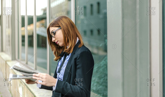 Businesswoman standing in front of wall- reading newspaper