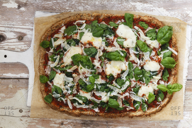 Gluten free pizza with cauliflower bottom- tomatoes and spinach leaves