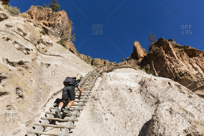 USA- New Mexico- Frijoles Canyon- Bandelier National Monument- Ruins and reconstructed kiva of the Ancestral Pueblo People- tourist on ladder towards Alcove House