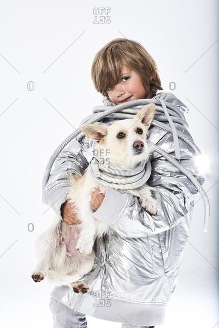 Portrait of a boy wearing fancy dress carrying dog
