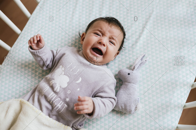 Portrait of crying baby girl lying in crib with toy bunny