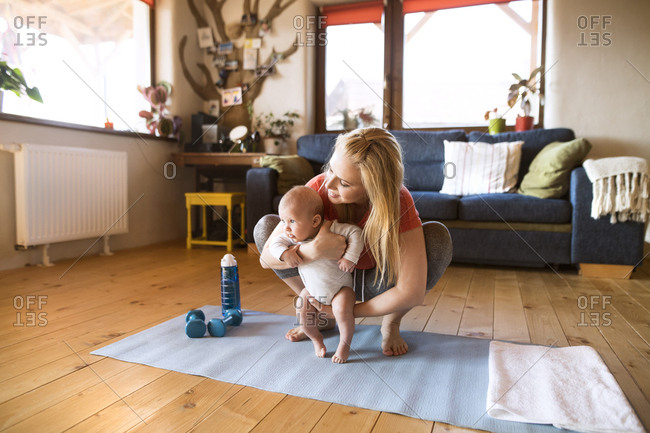 Mother with baby and dumbbells at home