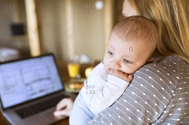 Mother with baby at home using laptop