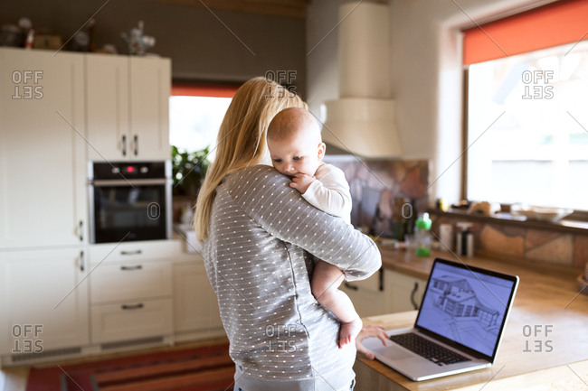 Mother with baby at home looking at house on laptop screen