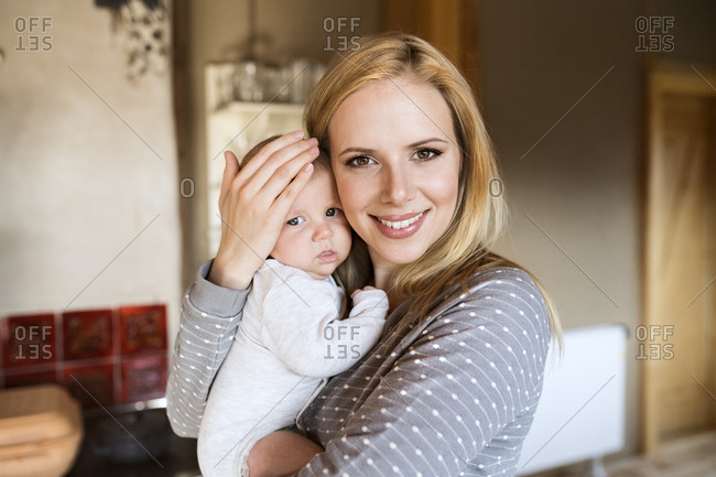 Portrait of smiling mother holding baby at home