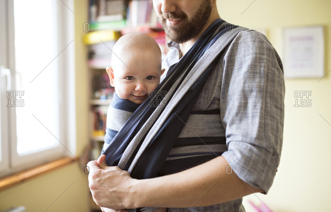 Father with baby son in sling at home