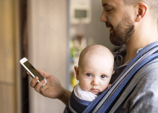 Father with baby son in sling at home using cell phone