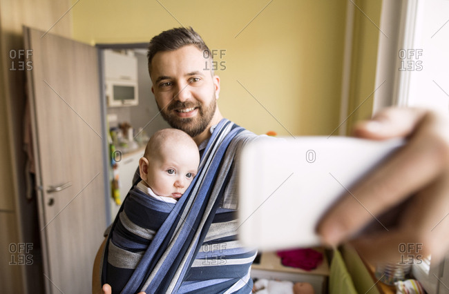 Father with baby son in sling at home taking a selfie