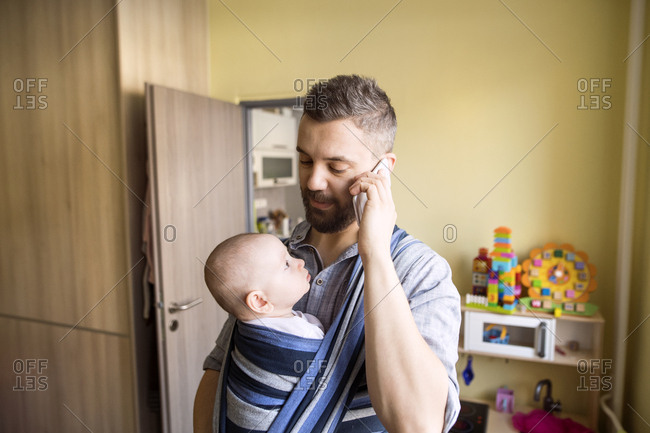 Father with baby son in sling at home talking on cell phone