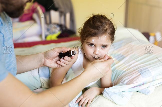 Girl having chickenpox receiving medicine in bed