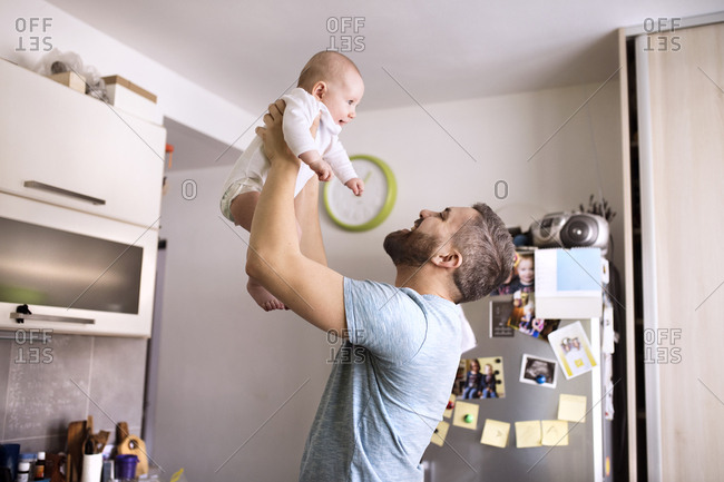 Father holding baby son in kitchen