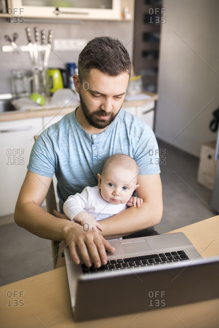 Father with baby son using laptop at home