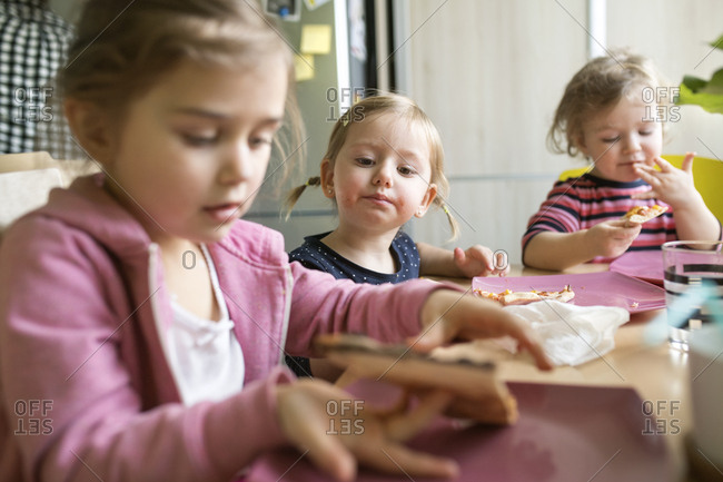 Little girls at home eating pizza