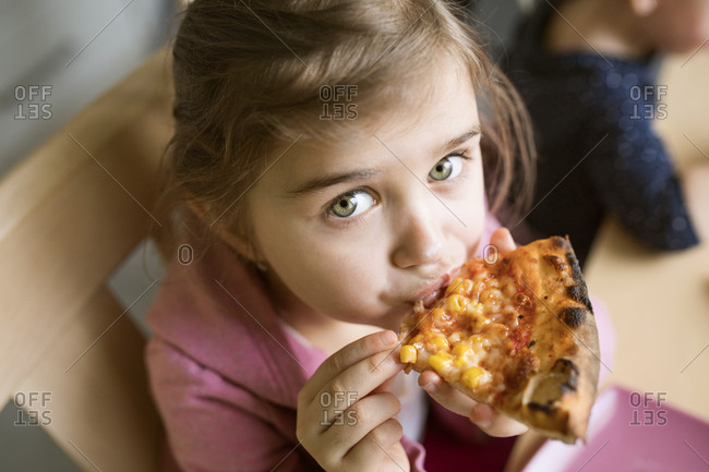 Little girl at home eating slice of pizza