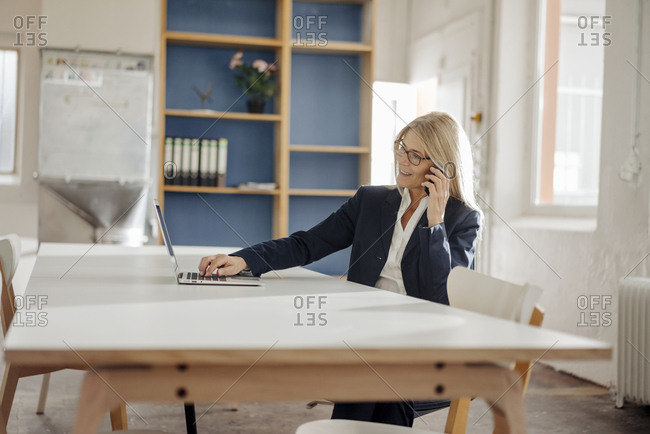 Businesswoman using laptop and cell phone in office