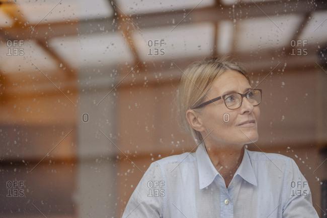 Businesswoman behind rainy windowpane looking away