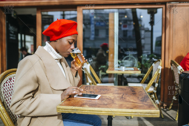 Young woman in Paris drinking beer in cafe and reading messages