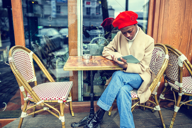Young woman in Paris reading menu in a cafe