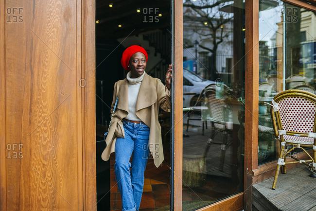 Young woman in Paris standing in door of a cafe