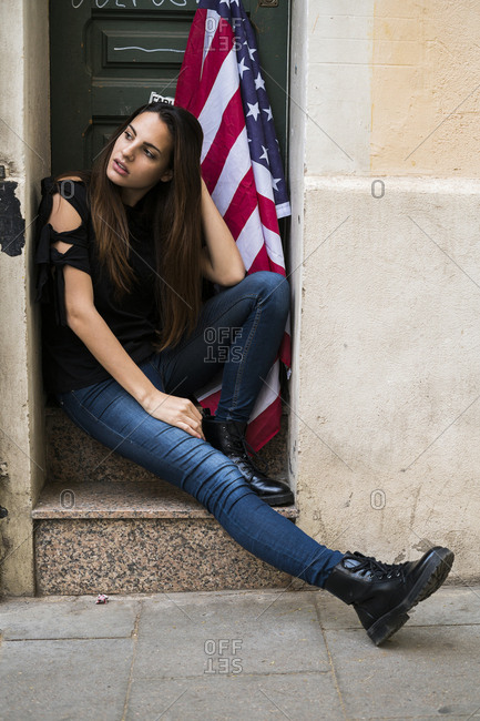 Portrait of young woman sitting at house entrance with US American flag
