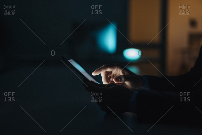Close-up of businessman working late in office using tablet