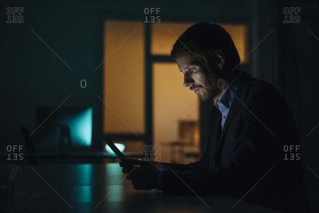 Businessman working late in office using tablet