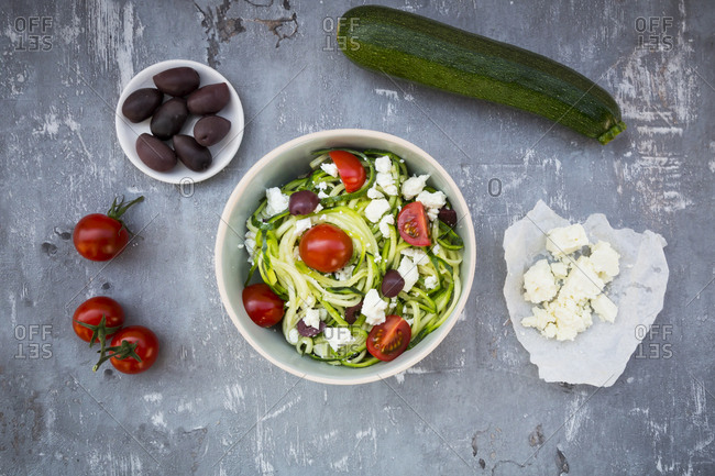 Bowl of zucchini spaghetti with feta- cherry tomatoes and black olives