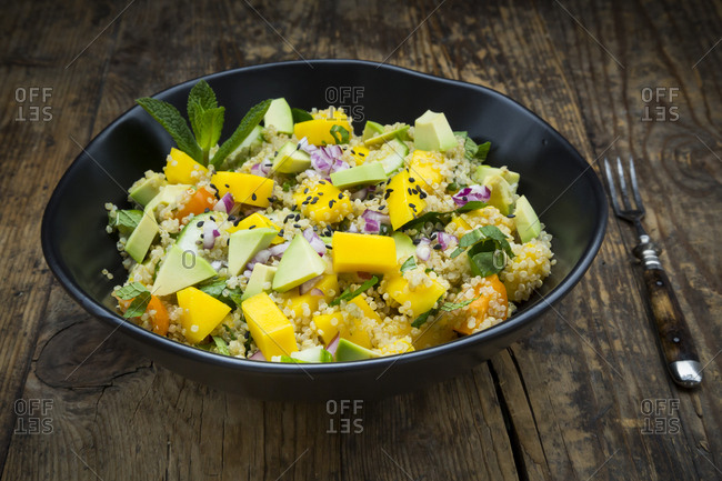 Bowl of quinoa salad with mango- avocado- tomatoes- cucumber- herbs and black sesame